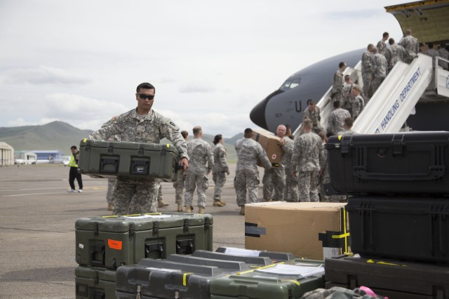 Alaska Army National Guardsmen Sgt. Edsel Huynh, 297th Battlefield Surveillance Brigade, carries medical supplies off a 168th Air Refueling Wing KC-135, after arriving in Ulaanbaatar, Mongolia, June 16, 2014. Approximately 100 Alaska Guardsmen are participating in Exercise Khaan Quest 2014, a multinational training exercise designed to strengthen the capabilities of U.S., Mongolian and other partner nations for effective participation in international peace support operations worldwide.