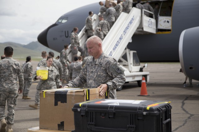 Alaska Army National Guardsman, Sgt. 1st Class John Nobles, 1st Squadron, 297th Cavalry Regiment (Reconnaissance and Surveillance), carries medical supplies off a 168th Air Refueling Wing KC-135, after arriving in Ulaanbaatar, Mongolia, June 16, 2014. Approximately 100 Guardsmen are participating in Exercise Khaan Quest, a platoon-through-battalion level, multinational peacekeeping operations exercise.