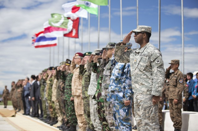 Service members from participating nations salute during the playing of the Mongolian National Anthem during the opening ceremony of Khaan Quest 2014, or KQ14, at Five Hills Training Area, Mongolia, June 20, 2014. KQ14 is a regularly scheduled, multinational exercise co-sponsored by U.S. Army Pacific, and hosted annually by Mongolian Armed Forces. KQ14 is the latest in a continuing series of exercises designed to promote regional peace and security.