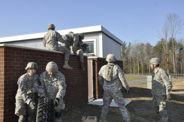 U.S. Army soldiers from the 82nd Airborne Division negotiate a wall obstacle at a school-like structure at the Asymmetric Warfare Training Center's Urban Complex while participating in an adaptability exercise hosted by the Asymmetric Warfare Group on March 1 at Fort A.P. Hill, Va. The adaptability exercise is one example of the many uses for the AWTC, which was built to enhance the AWG's mission of identifying capability gaps and providing rapid solution development within various complex operational environments. Adaptability and resiliency is one of the U.S. Army's major initiatives in developing its leaders.