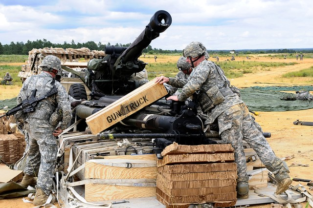 Paratroopers with the 2nd Battalion, 319th Airborne Field Artillery Regiment, 2nd Brigade Combat Team, 82nd Airborne Division, unpack an M119 Howitzer after an airdrop at Camp Mackall, North Carolina, during Joint Operational Access Exercise 13-03.