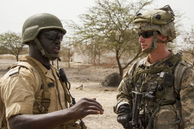 A Soldier from Burkina Faso and the U.S. discuss how to approach a mock food shortage riot during a situational training exercise, during Exercise Western Accord 14, June 24. Exercise Western Accord 14 is a U.S. Army Africa-hosted annual joint training and partnership exercise between the United States and Economic Community of West Africa States, which is designed to increase interoperability between military forces and ensure the common ability to conduct peace operations throughout Western Africa.