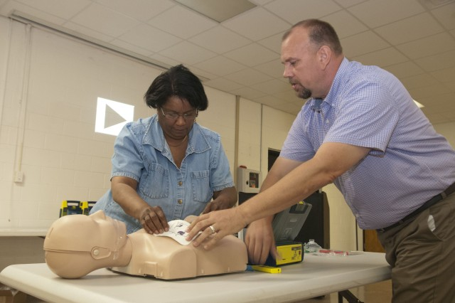 John Cobb, Cardiac Science educator and instructor for Automated External Defibrillator and Cardiopulmonary Resuscitation training, from Spanish Fort, Ala., demonstrates the proper placement of the AED defibrillator pads to Belinda K. Parker, 412th Theater Engineer Command's family programs coordinator from Prince George, Va., at the BG George A. Morris United States Army Reserve Center in Vicksburg, Miss. Ten Soldiers and civilians from the 412th participated in the three hour training and are certified to perform CPR and use the AED for two years. According to the 412th safety manager, Charlie Foreman, this training was important so the 412th is prepared in the case of an incident. (U.S. Army photo by Staff Sgt. Debralee Best)