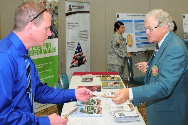 A civilian aide to the secretary of the Army takes a brochure about the Western Regional Medical Command at the 59th civilian aide to the secretary of the Army conference at Joint Base Lewis-McChord, Wash., June 24, 2014. At least one CASA represents Secretary of the Army John McHugh in each state and nearly all U.S. territories.