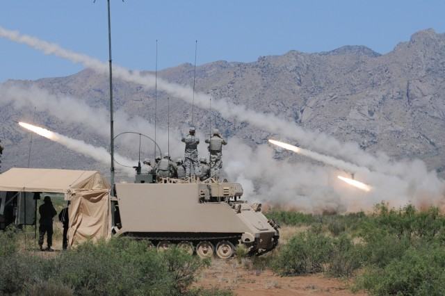 Members of the A Battery operations center and a local observer from Fort Bliss, Texas, stand atop their BACs to watch as launchers fire a volley of rockets. The final day of training consisted of a live-fire exercise in which over 100 rockets were fired over four hours in individual launches and time-on-target fires.