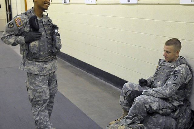 Sgt. Ashley V. Collo, 403rd Army Field Support Brigade, Korea, shares a light moment with Staff Sgt. Kevin A. Hopson, ASC headquarters, before competing in marksmanship early June 25 at the Rock Island Arsenal, Ill., indoor firing range. (Photo by Jon Micheal Connor, ASC Public Affairs)