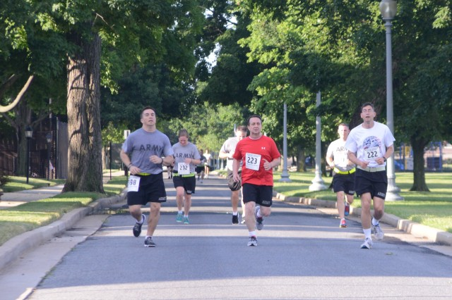 Runners race down 4th Avenue on Fort Lesley J. McNair during the Responders Race to Wellness run hosted by the United States Army Air Operations Group, June 26, 2014.