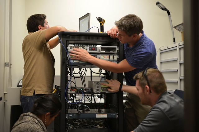 CERDEC Space and Terrestrial Communications Directorate engineers integrate modern protective equipment into an active circuit while simultaneously pulling out the legacy hardware.