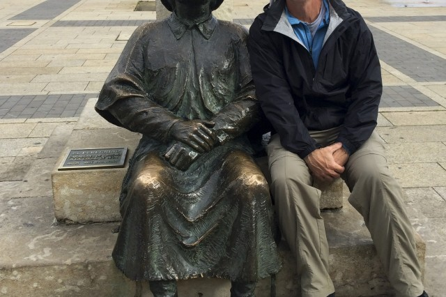 Barney Schulte, a structural engineer in the U.S. Army Corps of Engineers Nashville District, sits next to a statue of an ancient pilgrim resting his feet staring up at the San Marcos Parador May 22, 2014 in Leon, Spain. The shell on the hat of the pilgrim is an ancient symbol of the Camino.  Schulte visited this landmark during his 490-mile pilgrimage of Camino de Santiago, an ancient path that Christians retrace for spiritual renewal. (Photo by Mark Beckman)