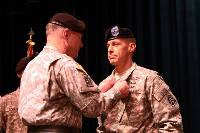 FORT SAM HOUSTON, Texas -- Lt. Gen. Perry Wiggins, commanding general for U.S. Army North (Fifth Army), and senior commander for Fort Sam Houston and Camp Bullis, pins the Legion of Merit medal on Maj. Gen. William Roy, deputy commanding general Army North, June 26 during a tattoo ceremony for Roy at the Fort Sam Houston Theater. The term tattoo dates from the Thirty Years War when drummers from the Dutch Army would go into the neighboring towns at 9:30 p.m. to inform the Soldiers that it was time to return to the barracks. The drum call, known as doe den tap toe (turn off the taps), was the signal for the innkeepers to stop serving beer and send the Soldiers home.
