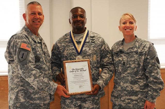 Command Sgt. Maj. Jean Thomas, NCOA commandant and 1st Sgt. Gloria Cain, NCOA deputy commandant, present Sgt. 1st Class Clenten Lewis with the bronze Order of Saint Michael award June 20 at the NCOA.