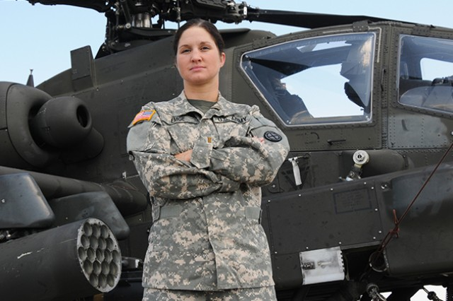 Second Lt. Justine Emge, D Company, 1-145th Aviation Regiment, poses in front of an Apache helicopter, June 18, 2014, at Fort Rucker, Ala. Emge represented the Army May 31, during the Armed Forces Triathlon Championship at Naval Base Ventura County, Point Mugu, Calif.