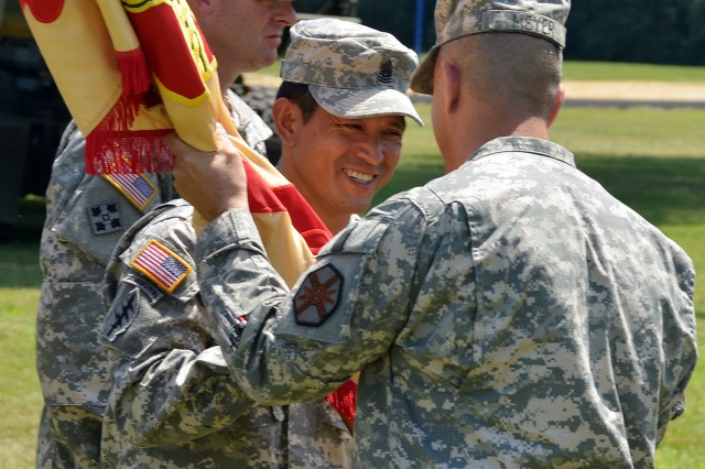 During the Change of Command, Change of Responsibility Ceremony June 27, Command Sgt. Maj. Weiquan A. Ho (left) accepts the U.S. Army Garrison Fort A.P. Hill colors from new commander Lt. Col. David A. Meyer signifying his assumption of responsibility for the garrison.