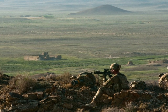 Spc. Eric Leveault, a native of Hollis, Maine, who serves as an infantryman for Charlie Company, 2nd Battalion, 504th Parachute Infantry Regiment, 82nd Airborne Division, monitors movement on the hilltops near his observation point overlooking the Darwazgay Pass in Zabul Province, Afghanistan, June 24, 2014. Leveault was part of a joint air assault mission conducted with the 1st Kandak, 2nd Battalion, 205th Corps, Afghan National Army, to disrupt weapons from coming into the area.