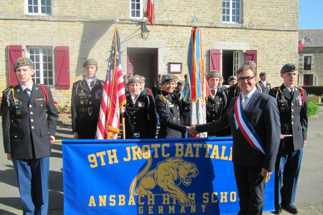 Arnaud Carré, mayor of Le Quiou, France, gives well wishes to the cadets of Ansbach Middle High School's 9th Junior ROTC Battalion before they leave for nearby Sainte-Mère-Église June 6, 2014. The cadets were there to commemorate the 70th anniversary of D-Day.