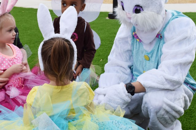 The Easter Bunny, Blake Armstrong, visits with children during the Family Child Care program's Easter Egg Hunt, April 18, at the Mountain Vista Community Center on Fort Huachuca. A number of FCC providers got together to offer this special program.
