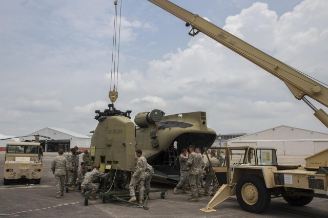 "Several Soldiers from 603rd Aviation Support Battalion, 3rd Combat Aviation Brigade assist in removing the aft pylon from a CH-47F Chinook helicopter during an emergency deployment readiness exercise held on Hunter Army Airfield June 23-27. The aft pylon holds the rear rotor, and has to be removed during the ""folding"" process the aircraft must go through in preparation to being loaded onto a C-17 Globemaster. (Photo by Sgt. William Begley, 3rd CAB Public Affairs)"