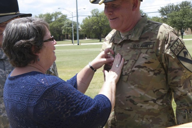 "Megan Bills, the wife of Maj. Gen. Michael Bills, commander, 1st Cavalry Division, adds the rank of major general to Bills' uniform during a promotion ceremony on Cooper Field at Fort Hood, Texas, June 27. Bills took command of the ""First Team"" in March and is headed to Afghanistan in support of Operation Enduring Freedom. (U.S. Army photo by Sgt. Angel Turner, 1st Cav. Div. PAO) (Released)"