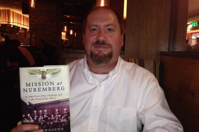 """Author Tim Townsend holds a copy of his book, """"Mission at Nuremberg,"""" during a recent interview in Washington, DC."""