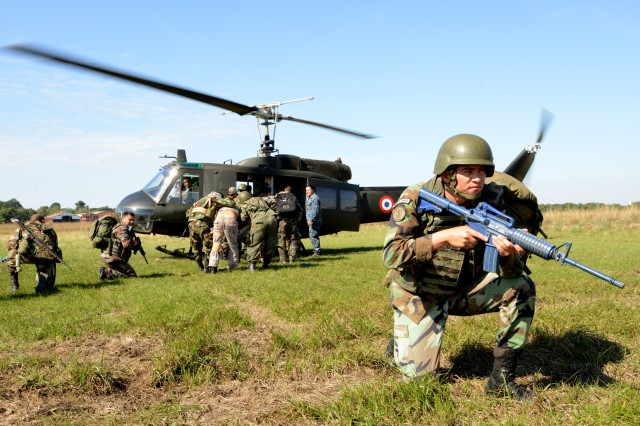 A Paraguayan special operations soldier provides security while his team rushes simulated casualties toward a Paraguayan air force UH-1 Huey helicopter during a simulated MEDEVAC exercise that was part of a tactical combat lifesaver course led by U.S. Army South in Asuncion, Paraguay, June 20.