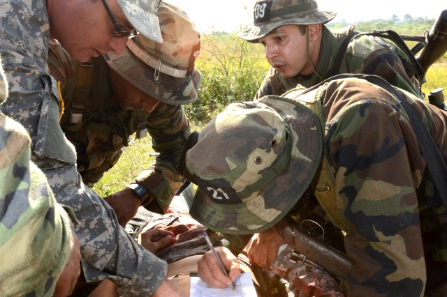 1st Lt. Norberto S. Montavi, Army Medical Command, 5501st U.S. Army Hospital, supervises Paraguayan special operations forces cadets as they give medical attention to a simulated casualty during a tactical combat lifesaver course June 20 in Asuncion, Paraguay. U.S. Army South led a team of U.S. medical professionals as they traveled to Asuncion June 16 -- 27 to conduct the course with more than 80 Paraguayan special operations forces soldiers.