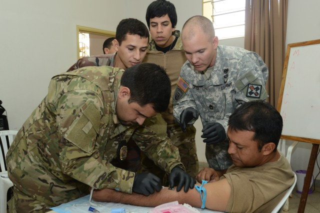 A Paraguayan soldier attempts to insert an IV into another soldier as Sgt. 1st Class Arnold Zarza, Defense Medical Readiness Training Institute, supervises during a tactical combat lifesaver course June 18 in Asuncion, Paraguay. U.S. Army South led a team of U.S. medical professionals as they traveled to Asuncion June 16 -- 27 to conduct the course with more than 80 Paraguayan special operations forces soldiers.