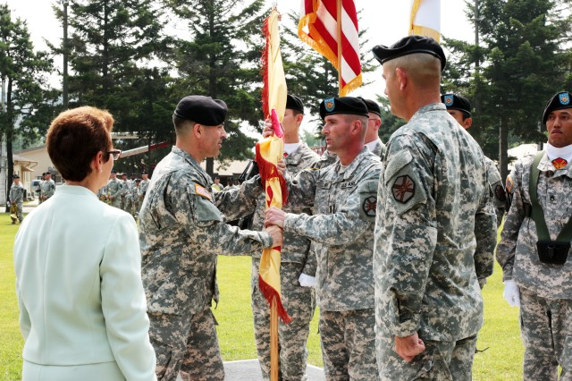 "At a change-of-command ceremony on Camp Red Cloud in Uijeongbu June 30, Col. Jack Haefner (second from left) assumes command of U.S. Army Garrison Red Cloud and Area I, replacing Col. John M. ""Mike"" Scott, (right, foreground, facing left), who led the garrison for nearly two years and moves to a new assignment at the Pentagon. Haefner passes the garrison's colors to Command Sgt. Maj. Patrick M. Quirk, the garrison's senior enlisted adviser. The ceremony's reviewing officer was Ms. Debra D. Zedalis (far left), Director, Installation Management Command-Pacific Region."
