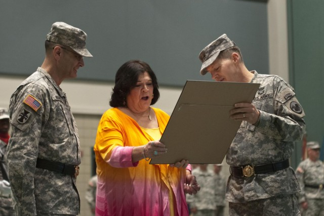 Mrs. Carol Buckler receives a gift from Lt. Gen. Jeffrey W. Talley, the chief of Army Reserve and commanding general of the U.S. Army Reserve, for selfless service to the Army as her husband, Maj. Gen. William Buckler, Maj. Gen. William M. Buckler Jr. (center), former 412th Theater Engineer Command commanding general, looks on during his retirement ceremony June 29. The 412th TEC conducted a change of command for incoming commander, Brig. Gen. Tracy A. Thompson and outgoing commmander, Buckler, a retirement ceremony for Buckler and a ceremonial promotion ceremony for Thompson at the Vicksburg Convention Center in Vicksburg, Miss,, June 29. (U.S. Army photo by Staff Sgt. Roger Ashley)