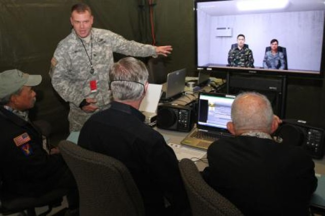 U.S. Army Staff Sgt. Michael Wadley, a virtual training instructor assigned to Headquarters and Headquarters Battalion, I Corps, explains the capabilities of an interrogation simulator to civilian aides to the secretary of the Army (CASAs) at Joint Base Lewis-McChord, Wash., June 24, 2014. At least one CASA represents Secretary of the Army John McHugh in each state and nearly all U.S. territories. (Photo by U.S. Army Staff Sgt. Christopher Klutts, 20th Public Affairs Detachment)