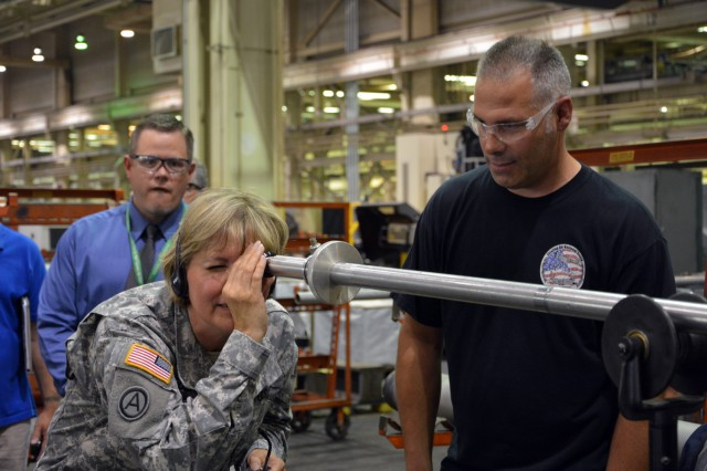 Lt. Gen. Patricia McQuistion, the AMC deputy commander, looking through a bore scope to see the type of quality control checks the arsenal does on each weapon tube, while Mike Merrill, from quality control explains the process.