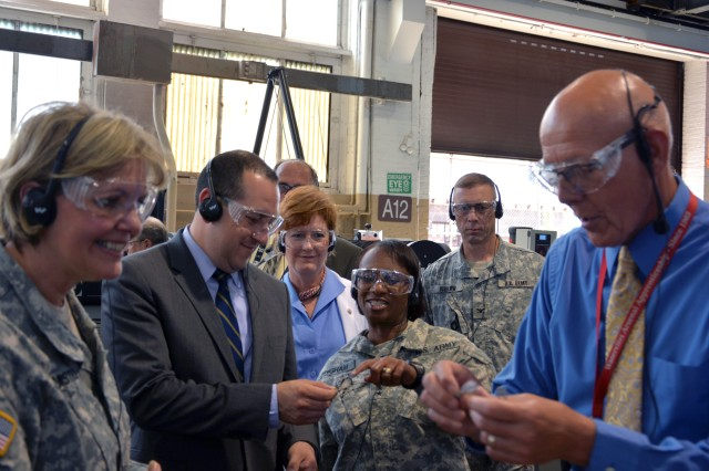 Maj. Gen. Gwen Bingham, the TACOM LCMC commander, in the center, talking to Mr. Gabriel Camarillo, the principal deputy at Office of the Assistant Secretary of the Army for Acquisition, Logistics and Techology, about a product produced by the waterjet machine.   Jake Peart, the arsenal's production planning and control supervisor, prepares to hand Lt. Gen. Patricia McQuistion a sample.
