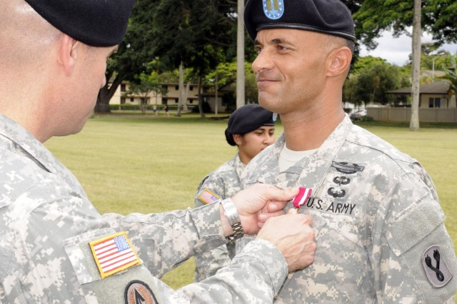 Col. Mark Jackson, commander, 8th Military Police Brigade, 8th Theater Sustainment Command, awarded Capt. Damon Adamson, Headquarters and Headquarters Company, 196th Infantry Brigade, the Meritorious Service Medal for exceptionally meritorious service from May 1991 to December 2014 during the 8th TSC's quarterly retirement ceremony held at Hamilton Field, here, June 27. (Photo by Staff Sgt. Richard Sherba, 8th Military Police Brigade Public Affairs, 8th Theater Sustainment Command)