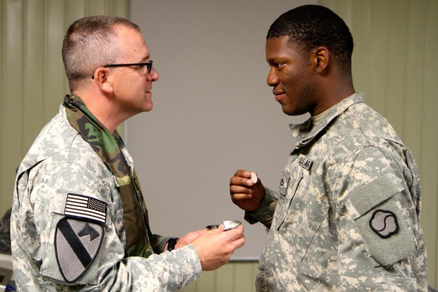 Capt. Robert L. Cook, Headquarters and Headquarters Detachment, 25th Transportation Battalion, 19th Expeditionary Sustainment Command chaplain gives a communion to Pfc. Brian A. Hendry, HHD, 25th TB, 19th ESC, S-1 administration specialist, during the crew gunnery exercise, June 26. Cook infused spiritual morale and strength to the Soldiers during the exercise.