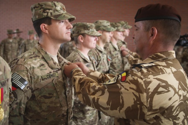 Lt. Commander Sean Conley, a native of Doylestown, Pa., who serves as an emergency physician and department head of trauma for NATO Role 3 Multinational Medical Unit, receives the Romanian Medal of Honor from the 20th Infantry Battalion, Black Scorpions commander, for his heroic actions in saving a Romanian soldier at Kandahar Airfield, Afghanistan, May 9, 2014. Conley and his team treated five Romanian soldiers injured in an improvised explosive device blast. (U.S. Navy photo by Lt. William Legg)