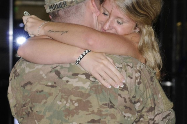 Alexandrea Hill, fiancée of Spc. John Parmer, 57th Military Police Company, 728th MP Battalion, 8th MP Brigade, 8th Theater Sustainment Command, jumps into the arms of her fiance and embraces him after a nine-month long deployment to Afghanistan. Parmer was a member of a 10-staff personal security detachment team that was honored in a redeployment ceremony, here, in the late hours of June 24. (Photo by Staff Sgt. Richard Sherba, 8th Military Police Brigade Public Affairs, 8th Theater Sustainment Command)