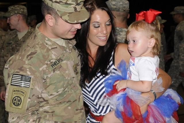 Sgt. Nathan Phelps embraces his wife, Kalan, and one-year-old daughter Peyton for the first time in nine months upon returning from a deployment to Afghanistan. Phelps was a member of a personal security detachment team that deployed to Afghanistan in support of Operation Enduring Freedom. The 10-staff personal security detachment team was celebrated and recognized in a redeployment ceremony held at Schofield Barracks, June 24. (Photo by Staff Sgt. Richard Sherba, 8th Military Police Brigade Public Affairs, 8th Theater Sustainment Command)