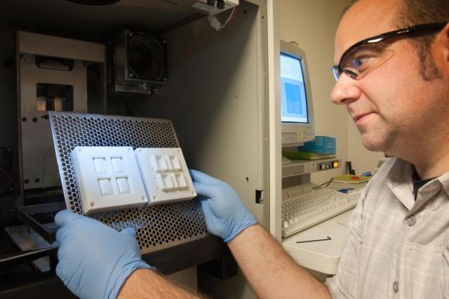 3-D modeling artist Bradley Ruprecht inspects parts of an injection molding hot off the printer.