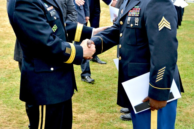 Lt. Gen. Donald M. Campbell Jr., U.S. Army Europe commander, congratulates Sgt. Danny S. Tuggle of Headquarters Company, 5th Signal Command, during the Hessentag ceremony.