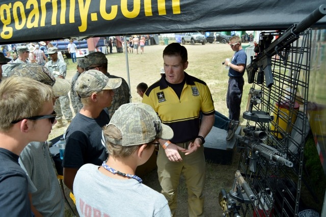 Sgt. Michael Howard, with the U.S. Army Marksmanship Unit Custom Firearm Shop, explains the different types of rifles and pistols used by the Army Marksmanship Unit, to attendees of the 2014 Country Jam at Grand Junction, Colo. Nearly 100,000 people attended the four-day concert. Recruiters from the Grand Junction-Denver Recruiting Battalion, the Mission Support Battalion and the Army Marksmanship Unit interacted with concert goers, June 19-22, 2014, in Grand Junction, Colo.