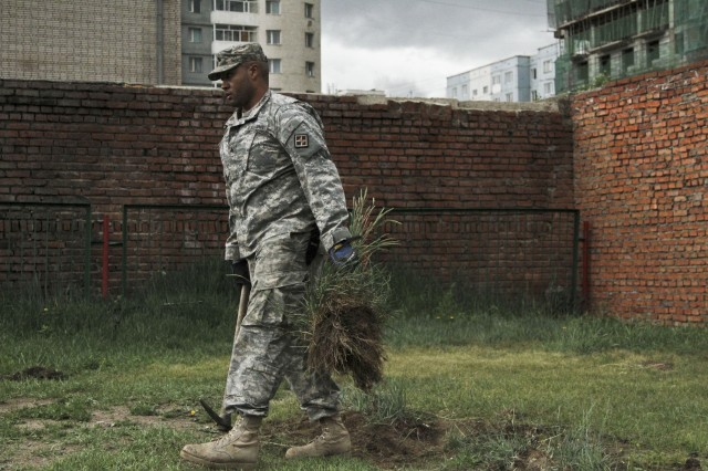 Sgt. Dale Brewster, a combat engineer with U.S. Army Reserves 465th Engineering Company (vertical) out of Birmingham, Ala., carries away weeds during a Khaan Quest 2014 Engineering Civic Action Program project at the 114th Kindergarten in Bayangol district, Ulaanbaatar, Mongolia, June 24, 2014. Khaan Quest is a multinational peacekeeping exercise co-sponsored by U.S. Army, Pacific, and U.S. Marine Corps Forces, Pacific, hosted annually by the Mongolian armed forces.