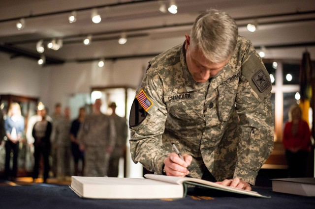 ROSE BARRACKS, Germany -- Sergeant Major of the Army Raymond F. Chandler III signs a registry book July 1, 2014, at Rose Barracks, Germany. Chandler was inducted into the Honorary Squadron of 2d Regiment of Dragoons, an honor bestowed to those who have served honorably while assigned to the 2d Cavalry Regiment throughout history.