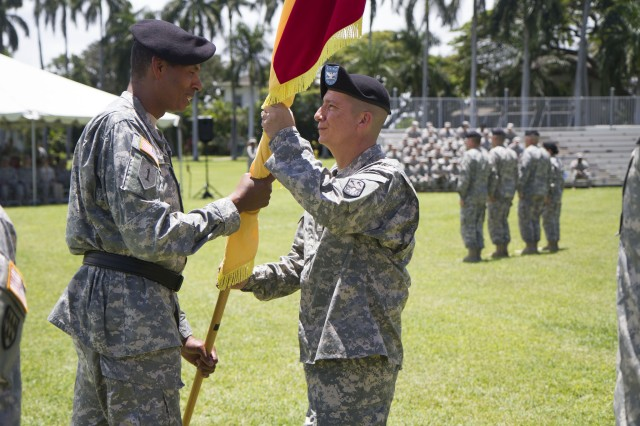 Gen. Vincent K. Brooks, commander, U.S. Army-Pacific  passes the 94th Army Air and Missile Defense Command's guidon to Col. Eric Sanchez, the new commander of the 94th AAMDC and promotable to Brig. Gen., during the unit's change of command ceremony, June 27, at Fort Shafter, Hawaii.  Sanchez' previous position was as deputy commander of the 32nd AAMDC at Fort Bliss, Texas.
