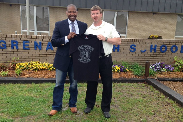 "Maj. Tony Winters (left), deputy logistics officer for First Army Division West, presents an ""Annihilator of Childhood Cancer"" character t-shirt to Jerry Williams, principal at Grenada High School in Grenada, Mississippi, during the days leading up to the inaugural Annihilator 5-K Run/Walk.  (Photo courtesy of Maj. Tony Winters, deputy logistics officer, First Army Division West)"