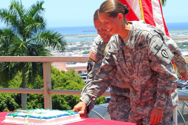 Brig. Gen. Dennis Doyle, Commnading General of Pacific Regional Medical Command, and 2nd Lt. Ann Elizabeth Moore, 25th Infantry Division, Medical Operations Officers, Division Surgeon Staff, make the first cut in the birthday cake to celebrate the Medical Service Corps' 97th birthday at Tripler Army Medical Center, Hawaii on June 30, 2014.