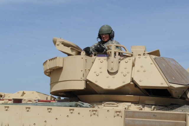 "Maj. Chrissy Cook, an engineer officer and S-3 for 3rd Brigade Engineer Battalion, 3rd Brigade Combat Team, 1st Cavalry Division, sits at the helm of her Bradley Fighting Vehicle July 7, 2014, at Fort Hood, Texas, during a media opportunity following the announcement of her crew winning the title of ""Top Gun"" in her battalion during a recently completed Table VI gunnery exercise."