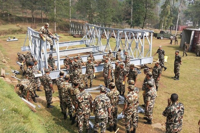Soldiers from the Nepalese Army assemble one of four Acrow roadway bridges that were recently delivered to Nepal as part of a foreign military sales, coordinated by the U.S. Army Security Assistance Command. The modular bridge system will be used for future humanitarian assistance and disaster relief.