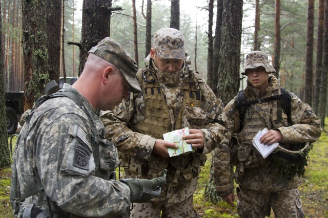 From left: U.S. Army Sgt. James Waller, and Latvian army Pfcs. Maris Vitenbergs and Gunarus Licis examine their compass and map prior to a land-navigation and emergency communications techniques training in Adazi, Latvia, July 1.
