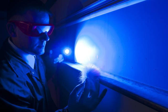 A CID Special Agent uses an alternate light source while processing a crime scene.