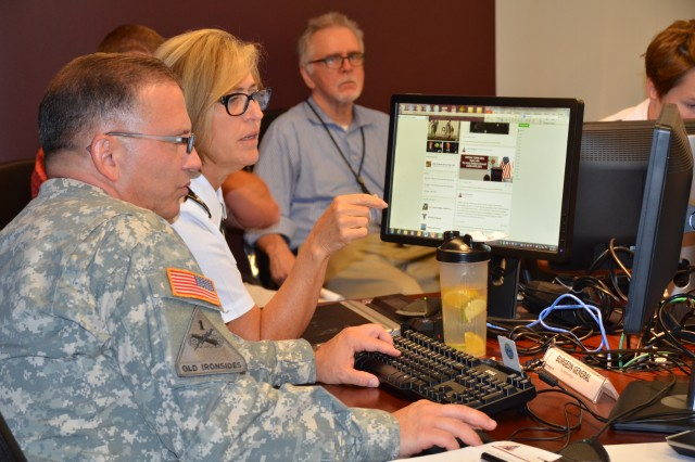 Lt. Gen. Patricia Horoho reads questions posted on Facebook during the Army Medicine Virtual Town Meeting, July 9, 2014. Her staff assists in answering a wide range of questions.