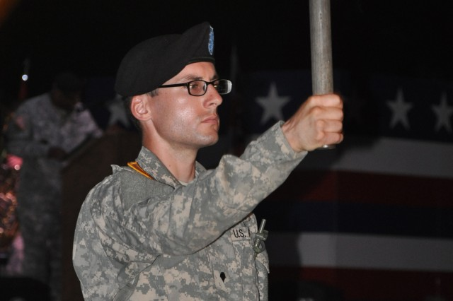 A Soldier holds a torch representing one of the 50 states and related territories during Fort Jackson's Torchlight Tattoo ceremony July 4, 2014 at Hilton Field.